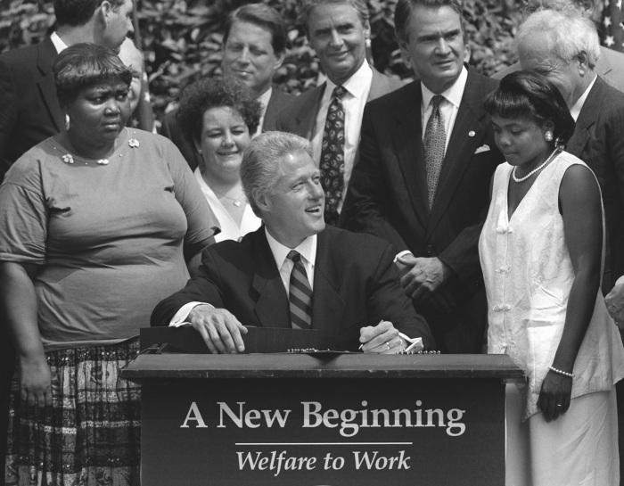 President Clinton prepares to sign legislation in the Rose Garden of the White House Thursday, Aug. 22, 1996, overhauling America's welfare system. Visible, from left, are former welfare recipients Lillie Harden, of Little Rock, Ark., and Janet Ferrel, of West Virginia, Vice President Gore, West Virginia Gov. Gaston Caperton, Sen. John Breaux, D-La., and former welfare recipient Penelope Howard, of Delaware. (AP Photo/J. Scott Applewhite)